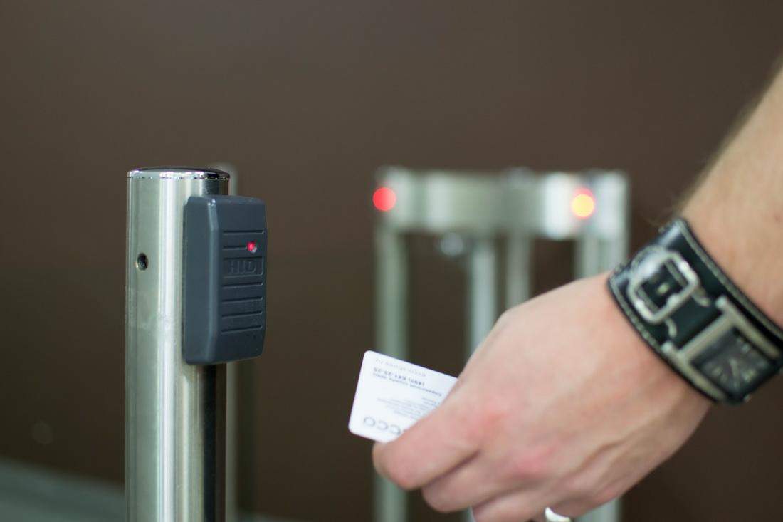 На фото сотрудник компании, с электронным ключом, проходит через систему контроля доступа.